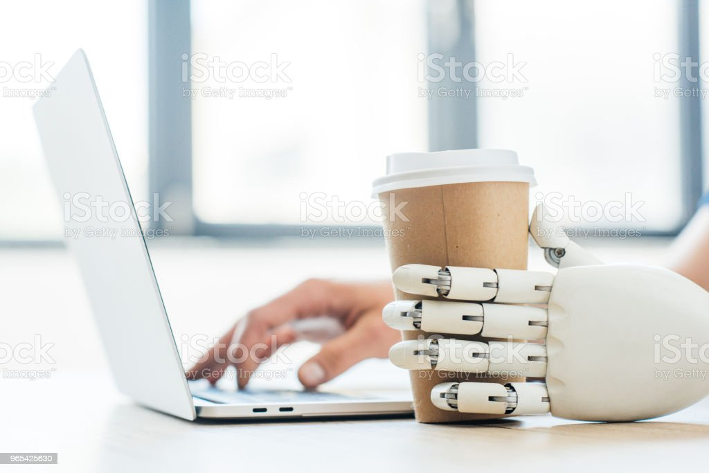 close-up view of robotic arm holding disposable coffee cup and human hand using laptop royalty-free stock photo