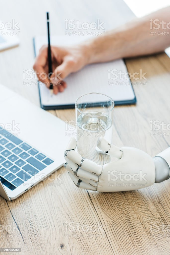 close-up view of robotic arm holding glass of water and person taking notes at wooden table royalty-free stock photo
