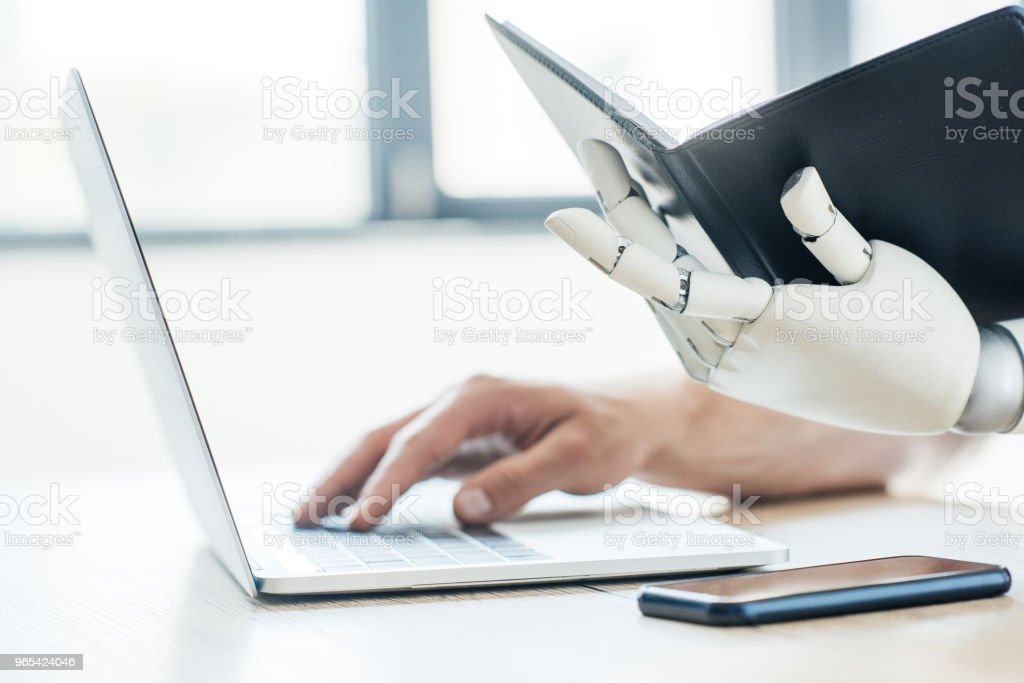 close-up view of robotic arm holding notebook and human hand using laptop at workplace royalty-free stock photo