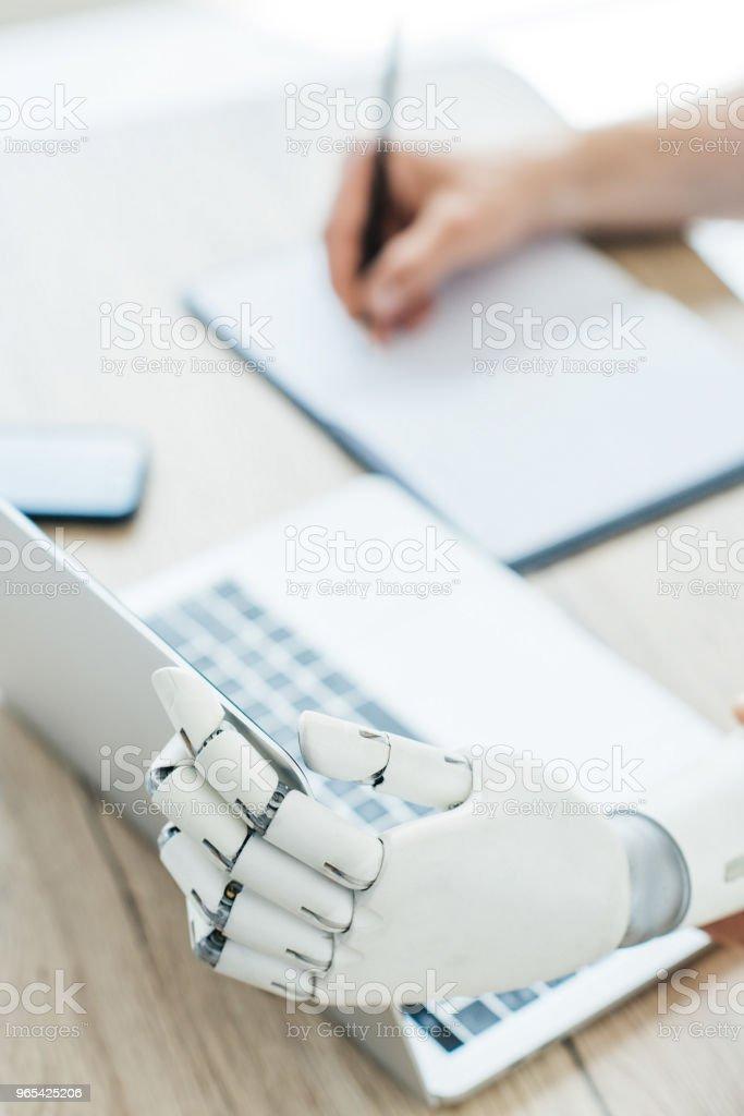 vue rapprochée du bras robotisé à l'aide d'ordinateur portable et la main de l'homme prendre des notes au milieu de travail - Photo de Artificiel libre de droits