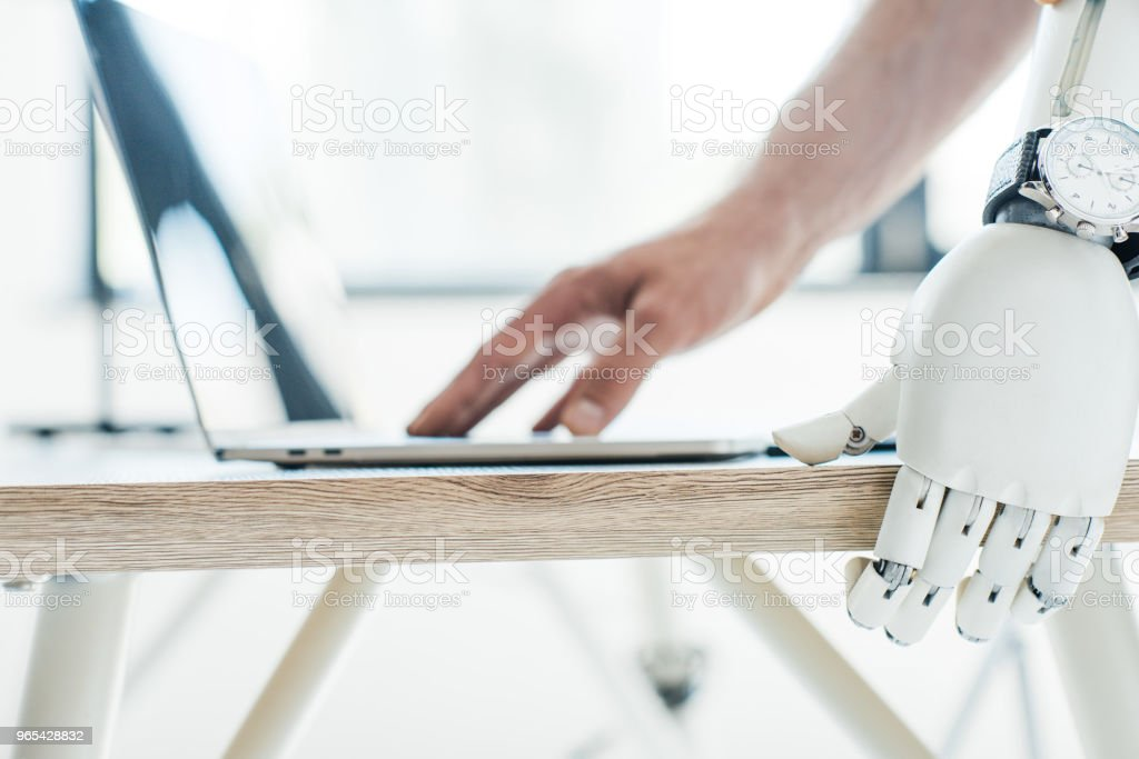 close-up vista do braço robótico com relógio de pulso, apoiando-se na mesa de madeira e a mão humana usando laptop - Foto de stock de Braço robótico royalty-free
