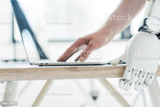 Foto de Closeup Vista Do Braço Robótico Com Relógio De Pulso Apoiandose Na Mesa De Madeira E A Mão Humana Usando Laptop e mais fotos de stock de Braço robótico