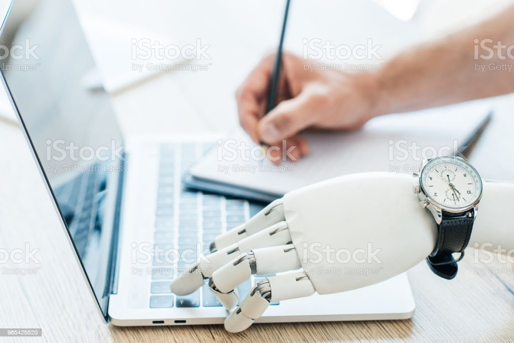 close-up view of robotic arm with wristwatch using laptop and human hand taking notes at wooden table zbiór zdjęć royalty-free