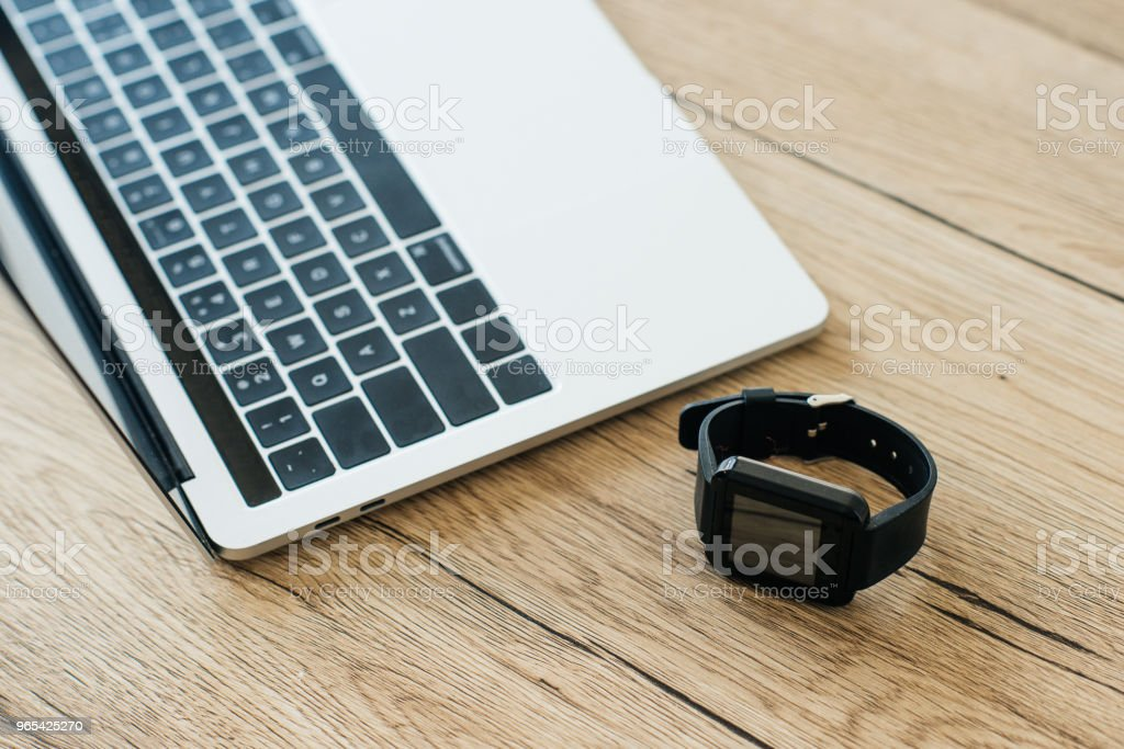Nahaufnahme von Smartwatch und Laptop auf Holztisch - Lizenzfrei Arbeiten Stock-Foto
