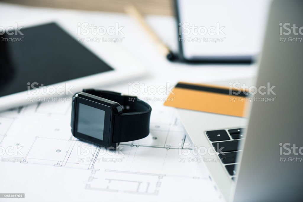 close-up view of smartwatch, laptop, digital tablet and blueprint at workplace zbiór zdjęć royalty-free