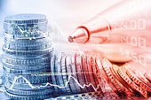 istock Closeup view of stack of coins, technical chart of financial instruments, a pen and a stock market price quotations. 675567878