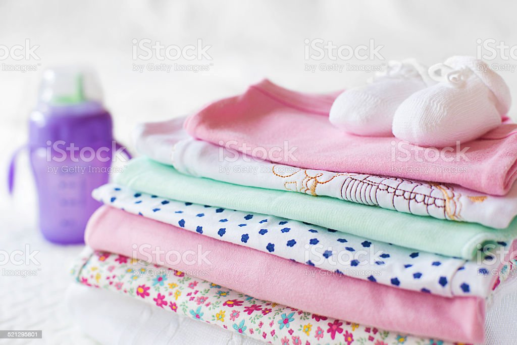 Close-up view of stacked baby clothing with a feeding bottle stock photo
