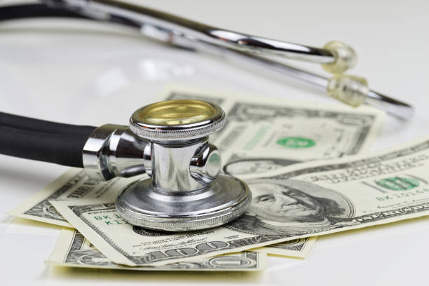 Close-up view of stethoscope and american dollars banknotes on white background stock photo