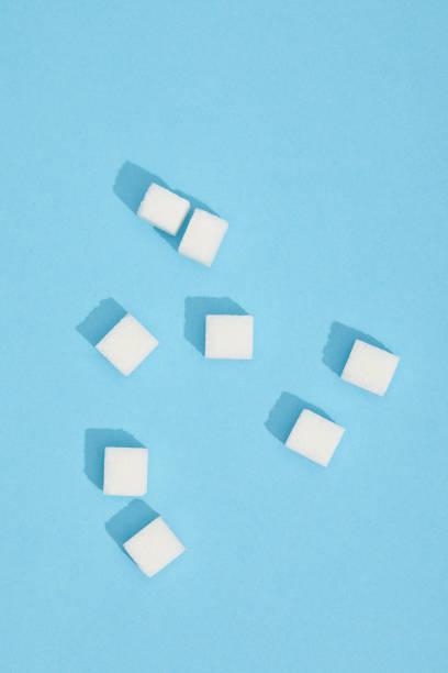 nahaufnahme der süßen weißen leckeren stück würfelzucker auf blau - würfelzucker stock-fotos und bilder