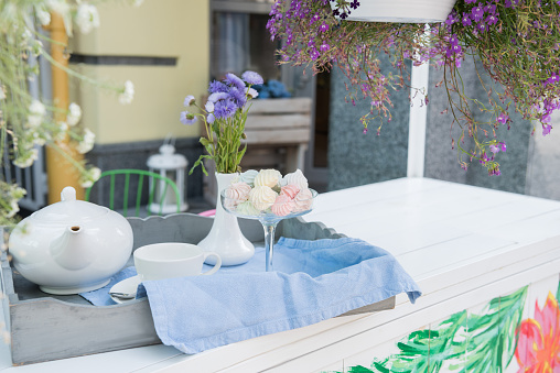 Close-up view of tea set with dessert and flowers in vase arranged on table in outdoor cafe
