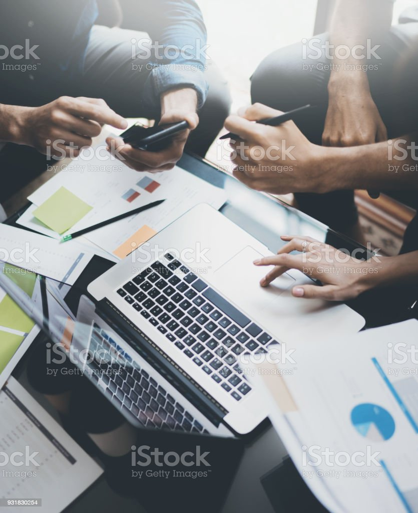 Closeup view of teamwork proccess.People hands, holding report paper documents, typing laptop.Vertical. stock photo