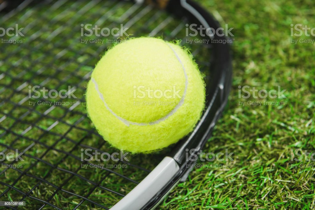 Close-up view of tennis racquet and ball on green grass stock photo
