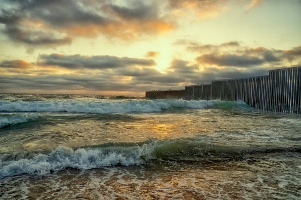 A Close-up View Of The Beach And Waves At Sunset Near The International Border Wall  In Playas Tijuana, Mexico A beautiful sunset on the beach near the border wall between Tijuana, Mexico, and the United States frontier field stock pictures, royalty-free photos & images