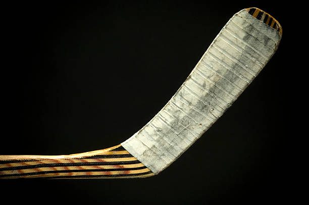 closeup view of the bottom of a hockey stick on a black back - hockey stick stock pictures, royalty-free photos & images