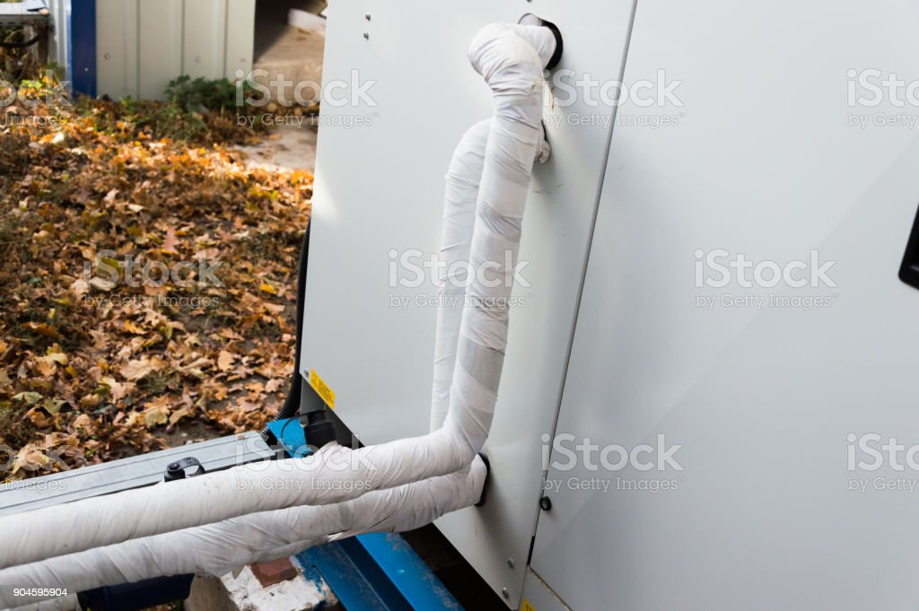 Close-up view of the insulated refrigerant pipelines connected to the air handling unit stock photo