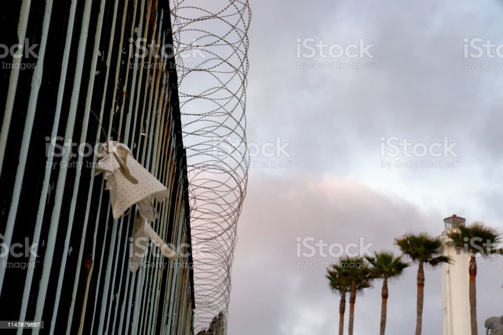 A beautiful sunset and palm trees with a closeup of the border wall...