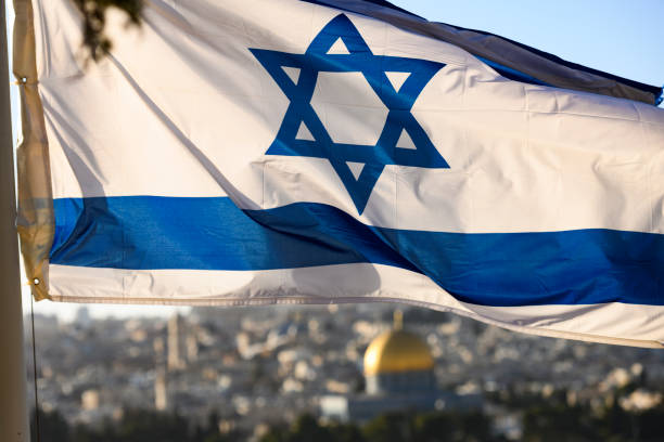 (focus on the flag) Close-up view of the Israeli flag with the  the blurred Dome of Rock and Jerusalem Old City in the background. (focus on the flag) Close-up view of the Israeli flag with the  the blurred Dome of Rock and Jerusalem Old City in the background. jerusalem old city stock pictures, royalty-free photos & images