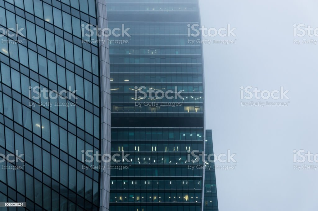 Close-up view of the modern skyscraper facade sin the mist stock photo