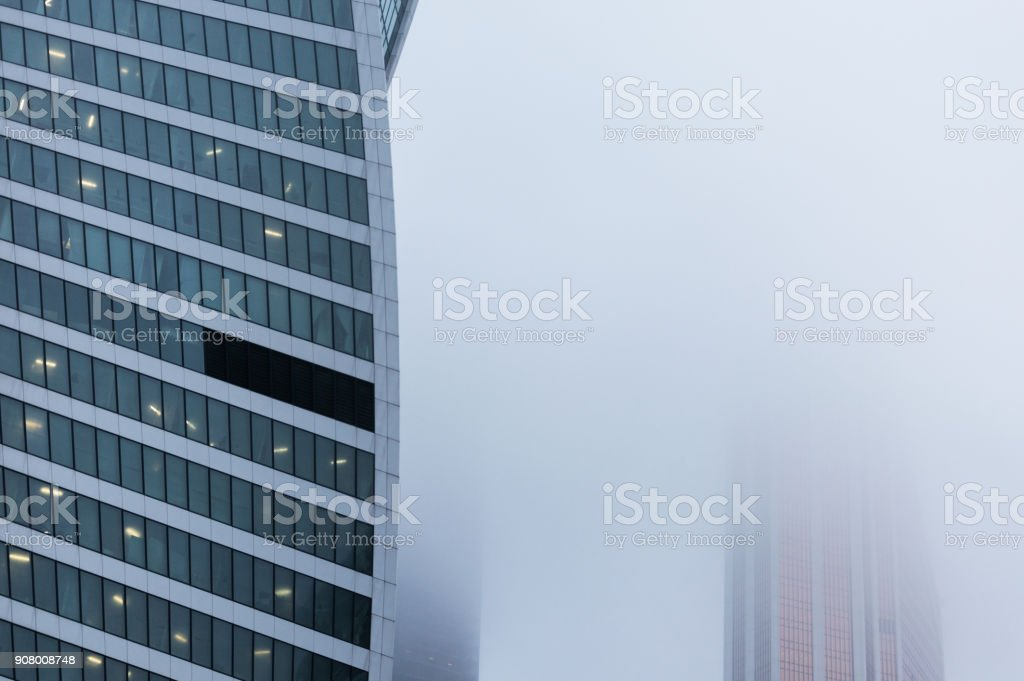 Close-up view of the side wall of the modern skyscraper standing into the fog stock photo