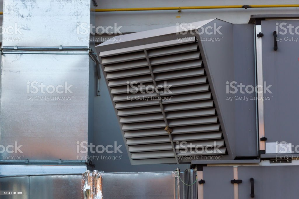 Close-up view of the ventilation louvres of the gray industrial ventilation unit standing outdoor stock photo