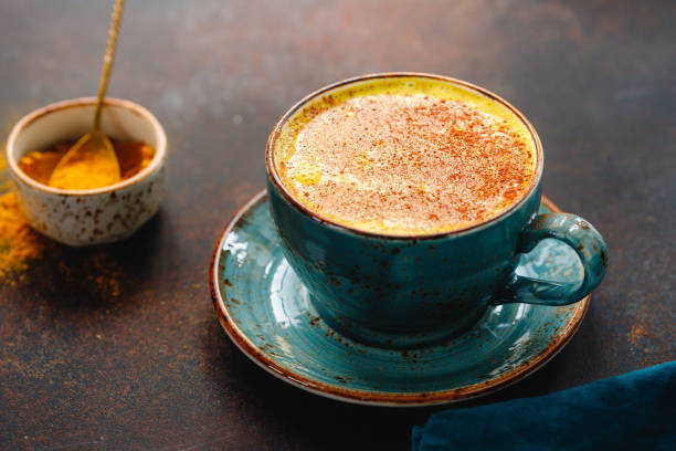 Closeup view of turmeric latte cup on a textured dark background. stock photo