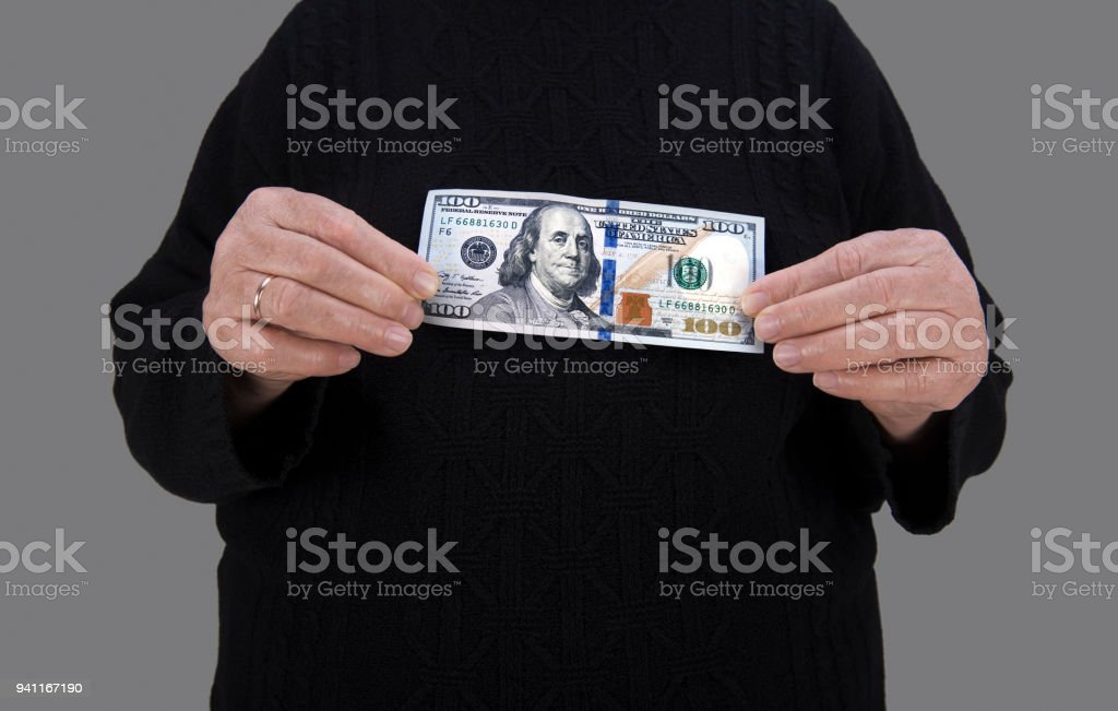 Close-up view of unrecognizable person holding a One Hundred American Dollar Bill stock photo