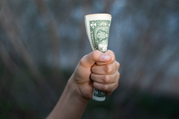 Close-up view of unrecognizable young woman gripping American One Dollar Bill. stock photo
