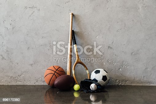 istock Close-up view of various balls and sports equipment near grey wall 696170380