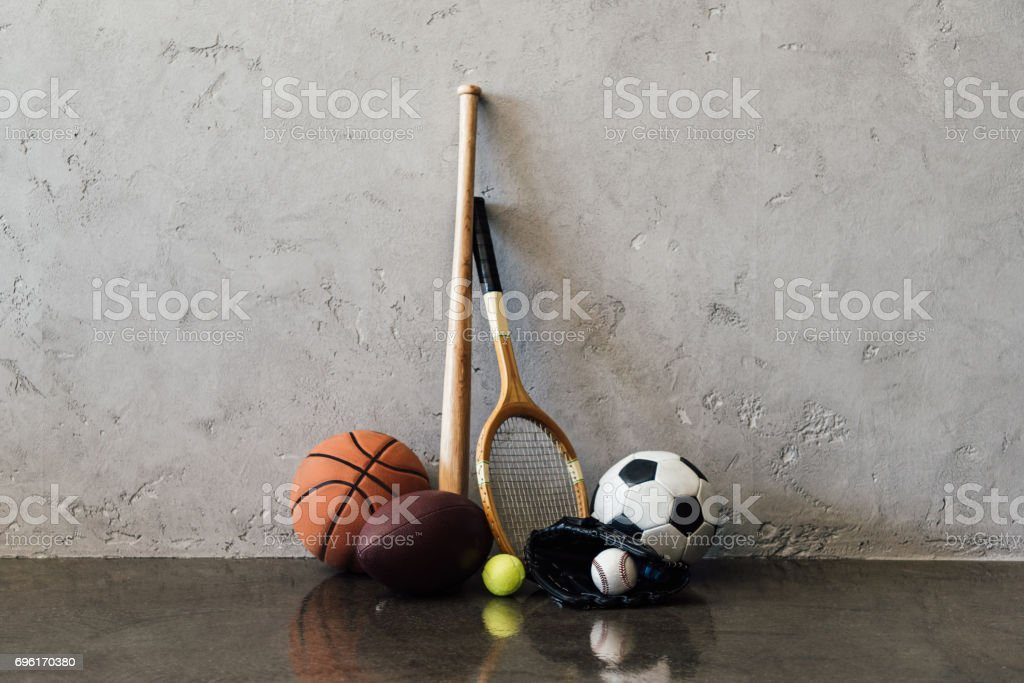 Close-up view of various balls and sports equipment near grey wall - foto stock