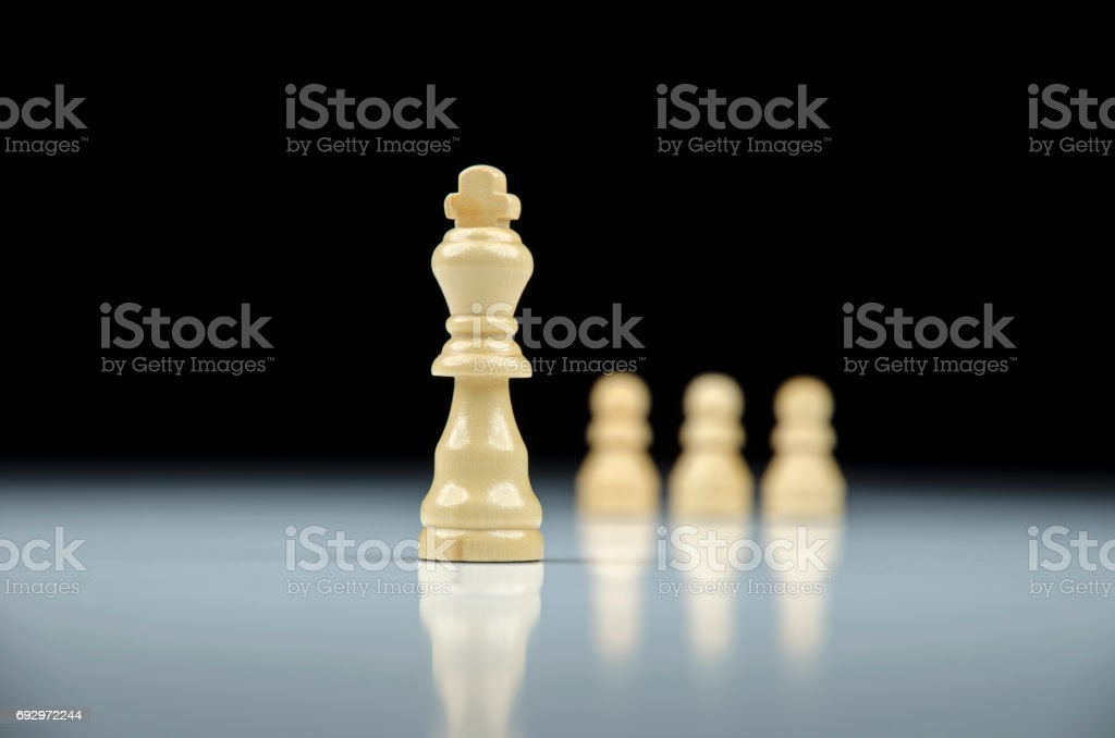 Close-up view of white chess king with white pawns on background on white background with reflection stock photo