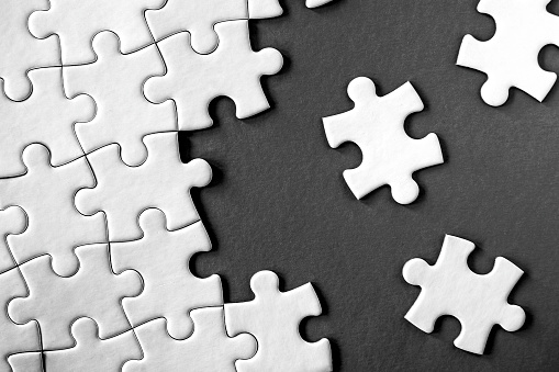 Close-up view of white jigsaw puzzle pieces on grey background