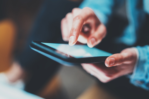 istock Closeup view of woman holding modern smartphone in hands.Girl typing on white touch mobile screen. Horizontal, blurred background, bokeh effects.Macro. 869376164