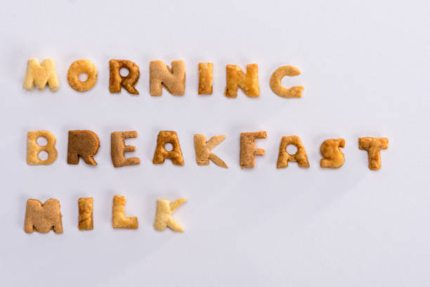 Close-up view of words morning, breakfast, milk from alphabet corn flakes isolated on grey stock photo