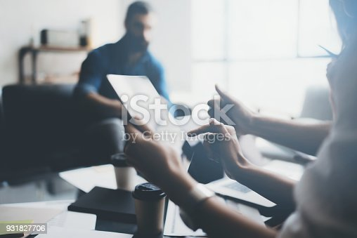 912675036 istock photo Closeup view of young coworkers working on laptop computer at office.Woman holding tablet and pointing on touch screen. Horizontal, blurred background. 931827706
