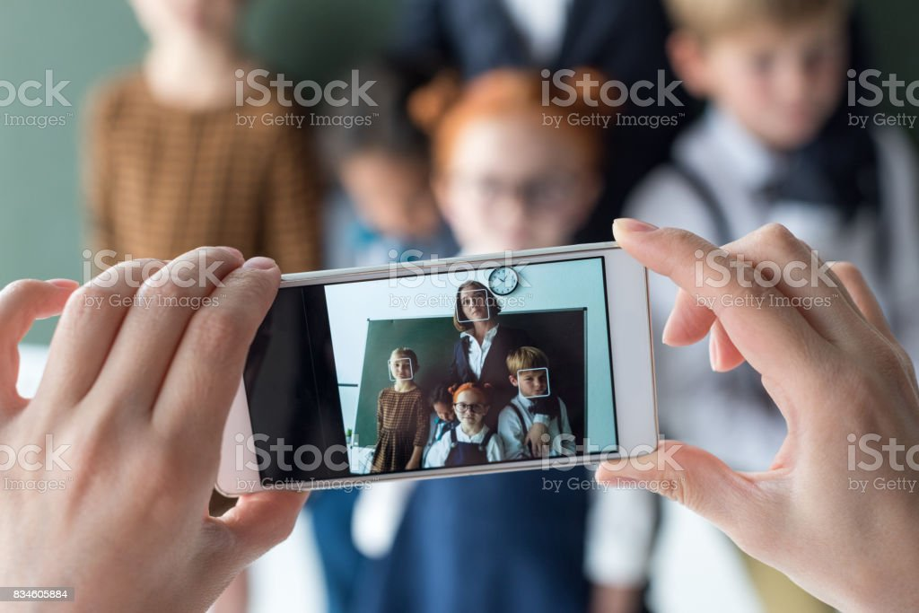 close-up view of young female teacher and cute little students photographing with smartphone stock photo