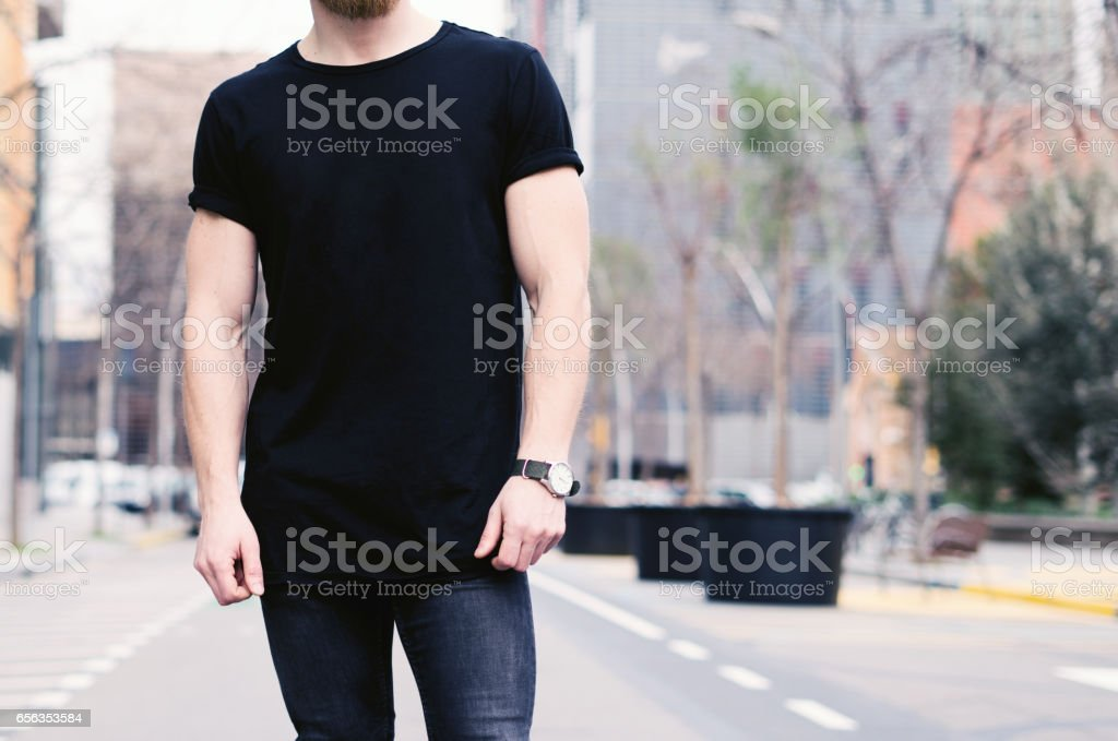 Closeup view of young muscular man wearing black tshirt and jeans posing on the street of the modern city. Blurred background. Hotizontal mockup. stock photo