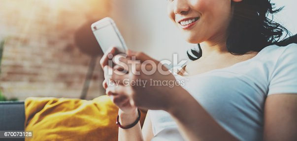 istock Closeup view of young smiling Asian woman sitting on sofa at home, wearing white tshirt and typing hands on smartphone.Horizontal blurred, flares effect.Wide.Selective focus. 670073128