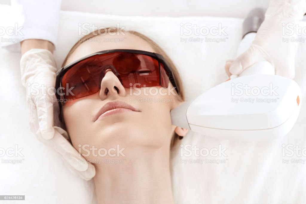 Close-up view of young woman in uv protective glasses receiving laser skin care on face royalty-free stock photo
