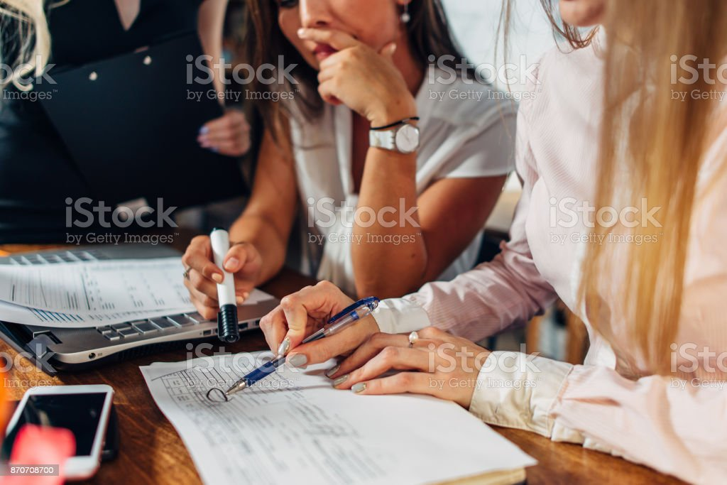 Close-up view of young women working on accounting paperwork checking and pointing at documents sitting at desk in office stock photo