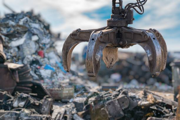 Close-up view on mechanical arm claw of crane at landfill. stock photo
