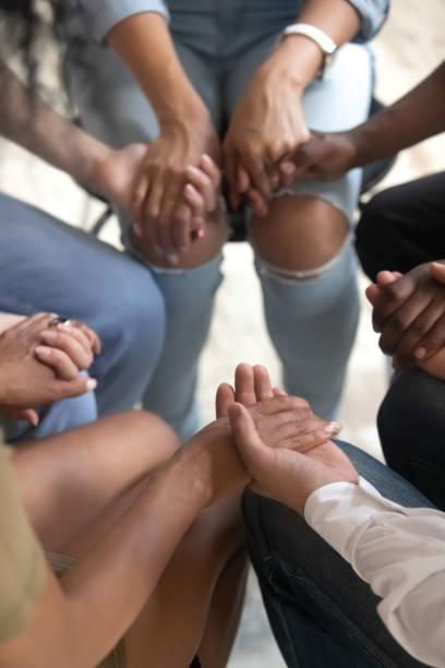 close-up te bekijken mensen zitten samen holding handen tijdens de therapiesessie - kleine groep mensen stockfoto's en -beelden
