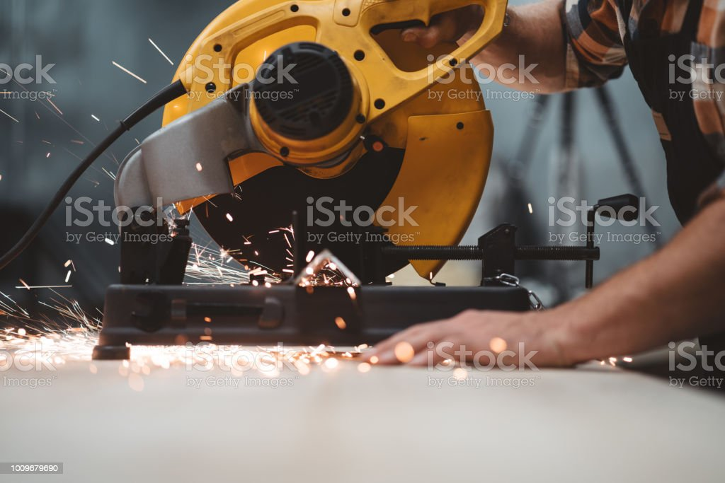 Close-up view strong hands of mechanic using electrical angular grinding machine at factory, sparks fly apart. Work in process on metalworking plant. Horizontal stock photo