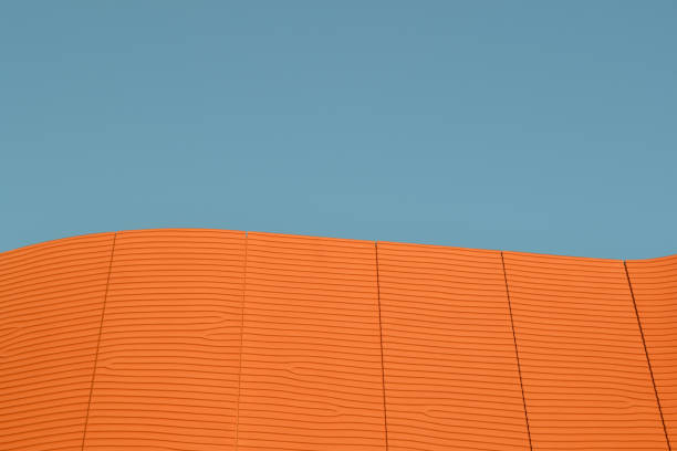 Close-up view to a modern asian architecture as a large brown cement wall brightly illuminated on the blue summer sky. stock photo