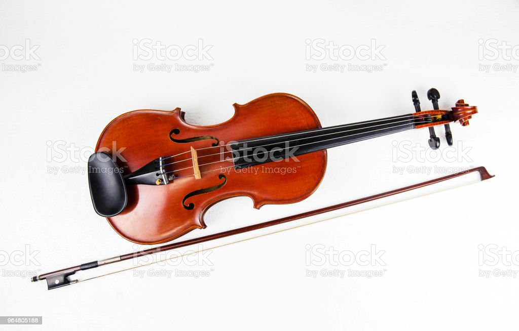 Closeup violin and bow put at the middle on white background.show detail of font side, royalty-free stock photo