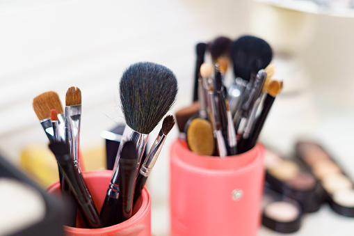 Makeup artist tools prepared for work. Set of cosmetic and airbrush over visagiste workplace background. Beauty, cosmetic and fashion. Professional makeup brushes and tools