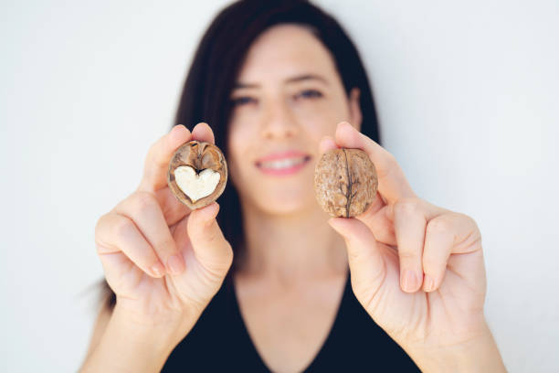 Close-up walnut half with a heart-shaped core in a female hand on the white background. Place for text stock photo