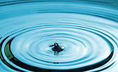 Closeup Water drop falling on the surface of the water and beautiful circular wave ripple, fresh natural mineral water drink water concept