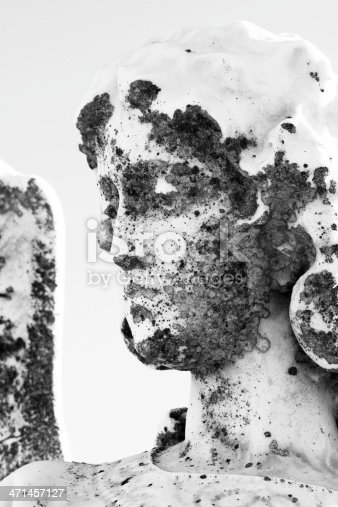 Closeup black and white weathered statue of angel, portrait, full frame vertical composition