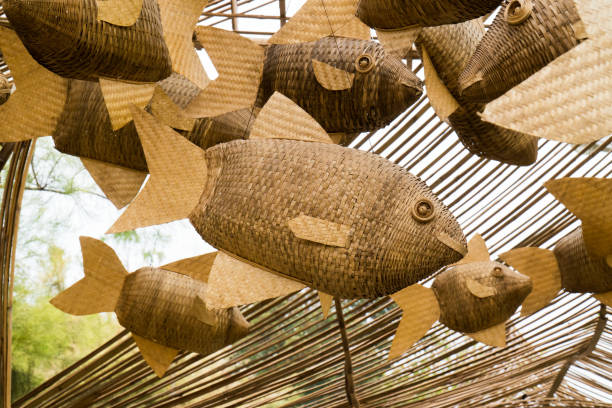 Closeup weave decoration wood fish mobile hanging at public park background. Group woven decorative bamboo wooden fish mobile suspend on wood ceiling roof frame Closeup weave decoration wood fish mobile hanging at public park background. Group woven decorative bamboo wooden fish mobile suspend on wood ceiling roof frame carving craft activity stock pictures, royalty-free photos & images