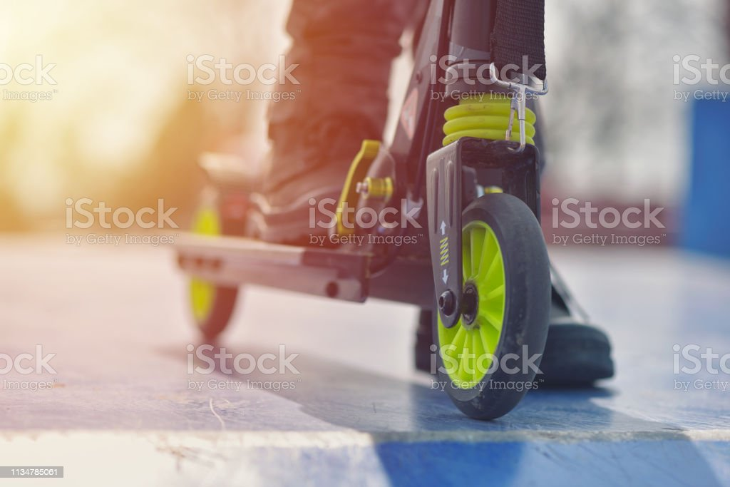 Close-up wheel from kick scooter on blue skatepark against warm sunset light - Foto stock royalty-free di Adolescente